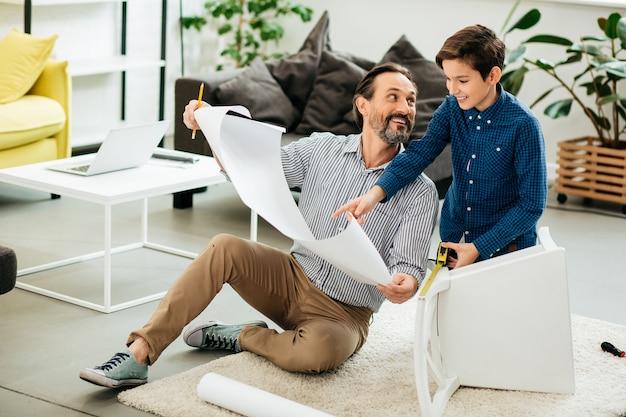 Vrolijke man zittend op de vloer en glimlachen terwijl zijn positieve zoon in de buurt zit met een meetlint en wijst naar de tekeningen in handen van vader