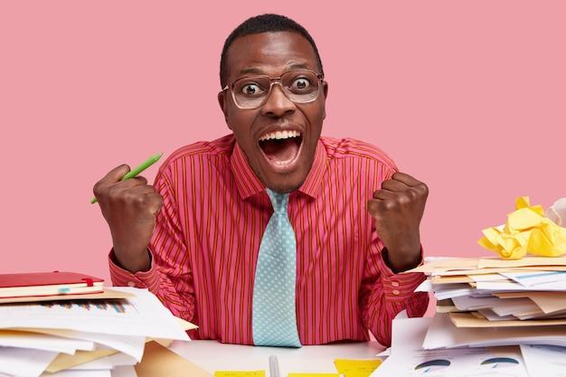 Vrolijke manager balde vuisten van geluk, houdt pen vast, roept vrolijk uit, zit op het bureaublad met documentatie, drukt zijn succes en triomf uit