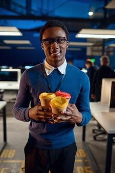Vrolijke manager houdt drie kopjes koffie, nachtelijke kantoorlevensstijl. mannelijke persoon op laptop, donker zakencentrum interieur, moderne werkplek modern