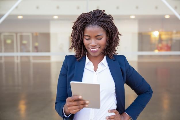 Vrolijke manager met tablet die goed nieuws krijgt