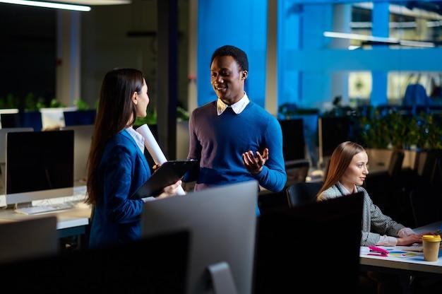 Vrolijke managers werken in nachtkantoor. glimlachende mannelijke en vrouwelijke werknemers, donker zakencentrum interieur, moderne werkplek modern
