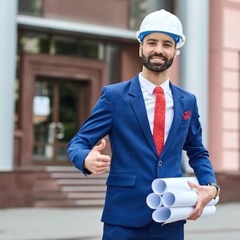 Vrolijke mannelijke architect die bouwvakker draagt die duimen toont die voor een gebouw stellen