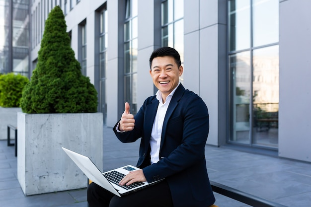 Vrolijke mannelijke aziatische zakenman die aan laptop online bankieren op computer in de buurt van kantoorcentrum werkt en naar de camera kijkt en glimlacht
