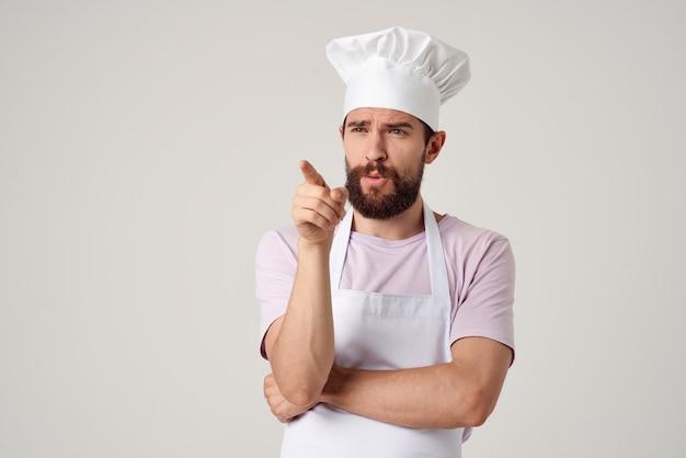 Vrolijke mannelijke chef-kok in uniform koken voedsel keuken lichte achtergrond