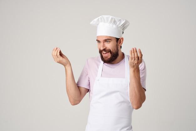 Vrolijke mannelijke chef-kok in uniforme gebaren met zijn handen gastronomisch restaurant