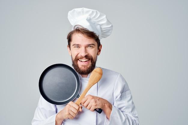 Vrolijke mannelijke chef-kok koekenpan in handen koken van voedsel professioneel koken. hoge kwaliteit foto