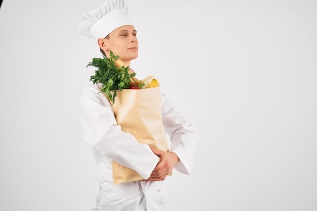 Vrolijke mannelijke chef-kok met een pakket gezonde voedingsproducten die keukendiensten bieden