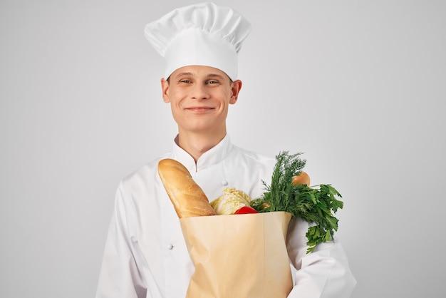 Vrolijke mannelijke chef-kok met een pakket producten die in de keuken werken