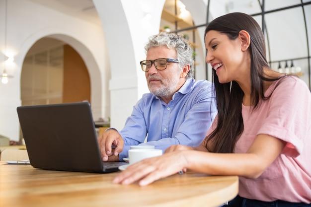 Vrolijke mannelijke en vrouwelijke collega's van verschillende leeftijden ontmoeten elkaar tijdens co-working, zitten op opengeklapte laptop, kijken naar inhoud