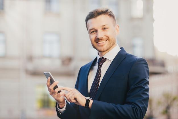 Vrolijke mannelijke financier houdt moderne mobiele telefoonchats met partners