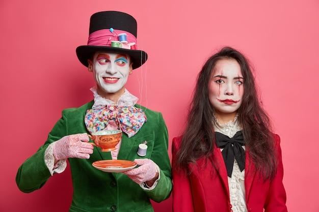 Vrolijke mannelijke hoedenmaker uit wonderland drinkt graag thee op feestje draagt grote hoed en groen jasje. ernstige vrouwelijke duivel met monsteroog en bloedige littekens