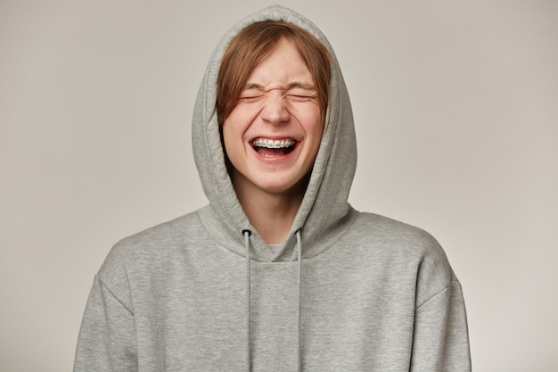 Vrolijke mannelijke, knappe man met blond haar. grijze hoodie dragen. heeft beugels. mensen en emotie concept. zet capuchon op en lacht met gesloten ogen. stand geïsoleerd over grijze muur