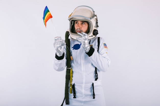 Vrolijke mannelijke kosmonaut in ruimtepak en helm, met lgtbi-regenboogvlag, op witte achtergrond.