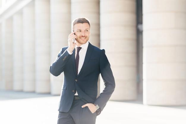 Vrolijke mannelijke ondernemer heeft telefoongesprek