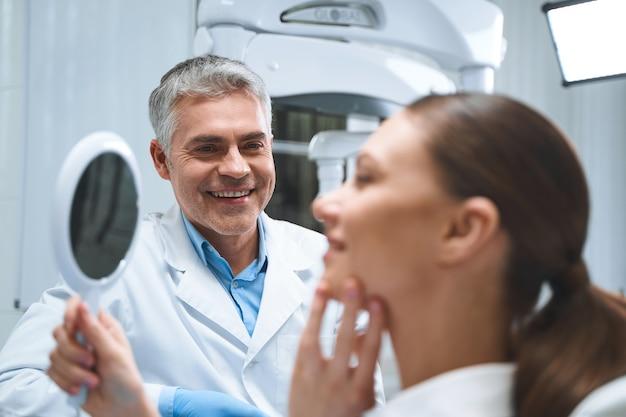 Vrolijke mannelijke specialist geniet van het werk met vrouwelijke patiënt terwijl ze na de behandeling in de spiegel kijkt
