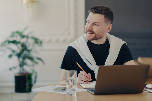 Vrolijke mannelijke student zoekt informatie voor huiswerk via laptop schrijft artikel zit in coworking space alleen kijkt weg met een gelukkige glimlach op gezicht horloges training webinar creats persoonlijke blog