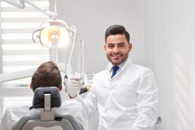 Vrolijke mannelijke tandarts glimlachen tijdens het werken met een patiënt op zijn kantoor