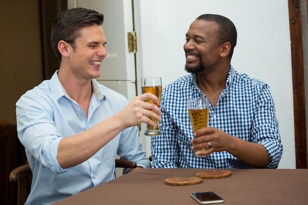 Vrolijke mannelijke vrienden roosteren bierglazen in restaurant