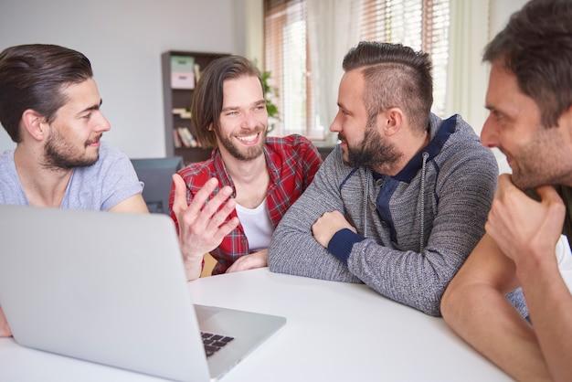 Vrolijke mannen achter de laptop zitten