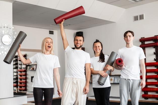 Vrolijke mannen en vrouwen staan met moderne gymmatten in handen in een fitnessstudio. groepsstretch, pilates of yogatraining.