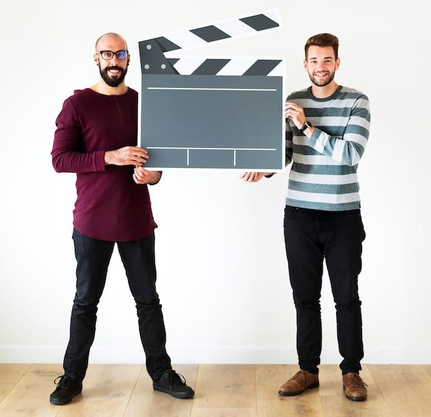 Vrolijke mannen houden klepel bord pictogram Premium Foto