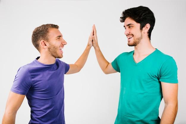 Vrolijke mannen in heldere t-shirts die high five geven