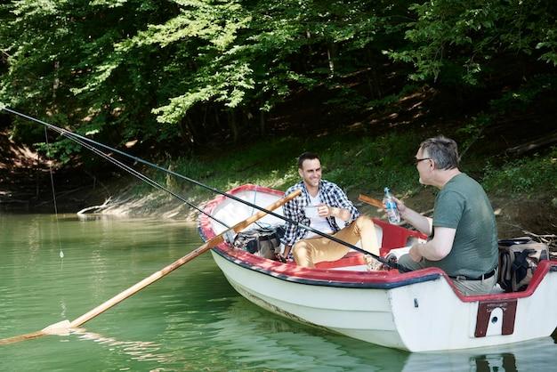Vrolijke mannen vissen aan een meer