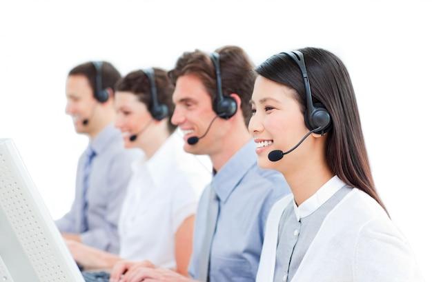 Vrolijke medewerkers van de klantenservice werken in een callcenter