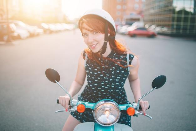 Vrolijke meisje drijfautoped binnen in stad. portret van een jonge en stijlvolle vrouw met een bromfiets