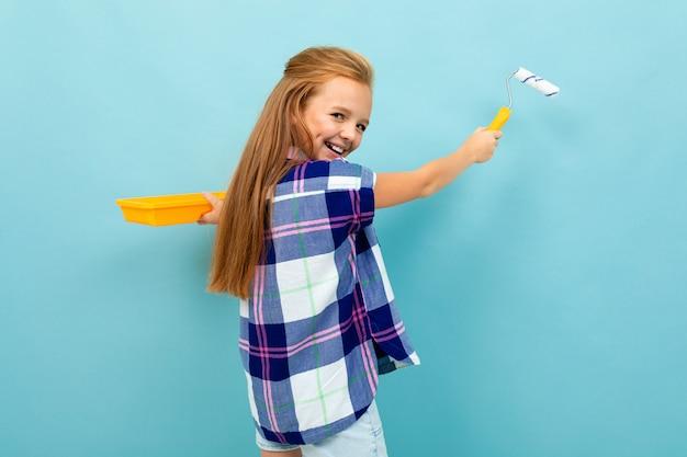 Vrolijke meisje schildert een muur met een roller en kijkt naar de camera