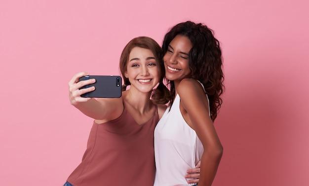 Vrolijke meisjes die een selfie nemen terwijl ze gebaar samen over roze tonen.