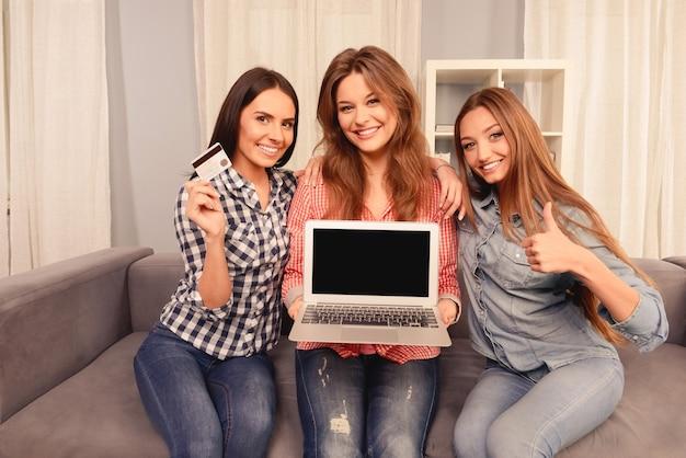 Vrolijke meisjes die laptop, bankkaart en gebaren tonen