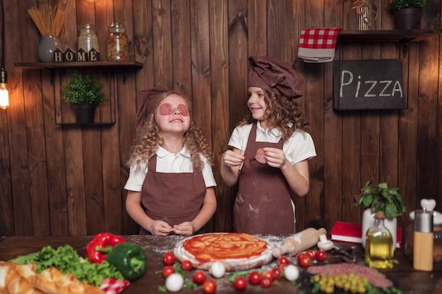 Vrolijke meisjes die pret met worst in keuken hebben