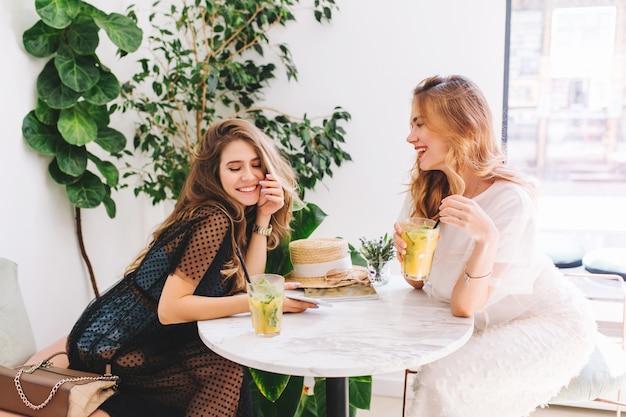 Vrolijke meisjes in elegante jurken en trendy accessoires die tijd doorbrengen en iets leuks bespreken