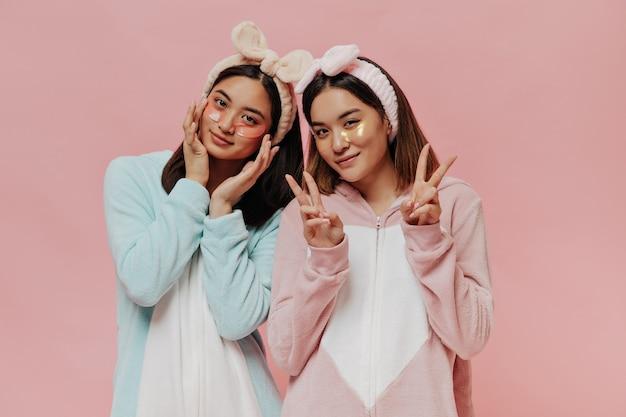 Vrolijke meisjes in kleurrijke zachte kigurumi's en cosmetische hoofdbanden laten v-tekens zien en doen een ochtendschoonheidsroutine