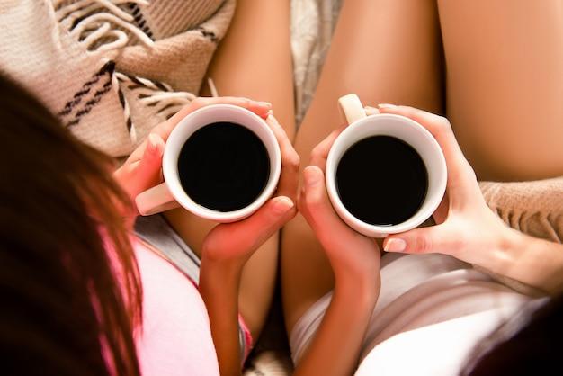 Vrolijke meisjes in pyjama's met koffie