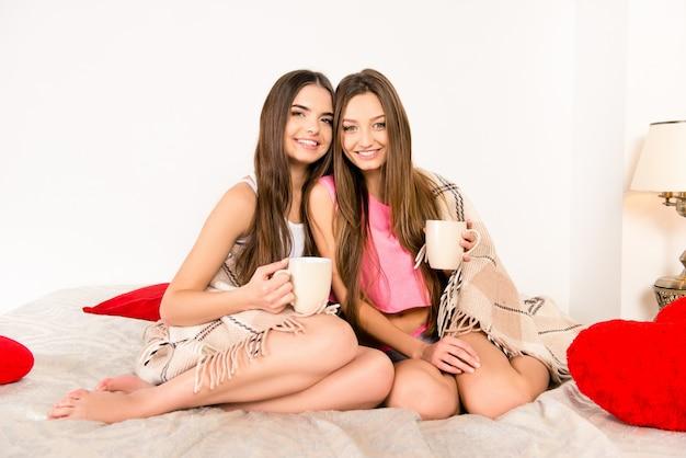 Vrolijke meisjes in pyjama's zitten in plaid met cups