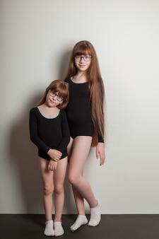 Vrolijke meisjes in sportmaillots staan op een zwarte yogamat met weelderige pannenkoeken en gezond haar. gelukkige zusters, portret op een witte achtergrond.