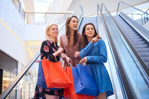 Vrolijke meisjes in winkelcentrum tijdens grote shopping