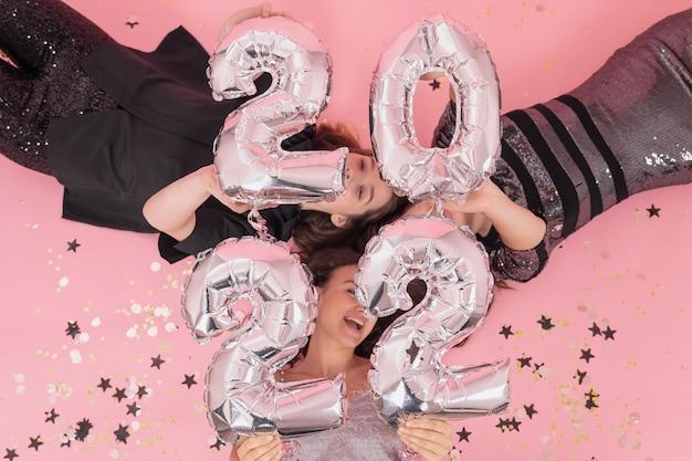 Vrolijke meisjes liggen op roze achtergrond met zilveren ballonnen bovenaanzicht