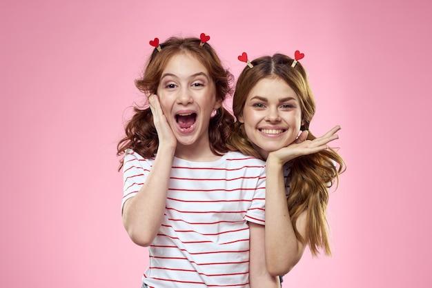 Vrolijke meisjes met modieuze sieraden op hun hoofd op roze