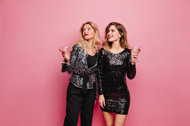 Vrolijke meisjes met wijnglazen die zich op rooskleurige muur bevinden. verbluffende vriendinnen in glamoureuze kleding die iets vieren.