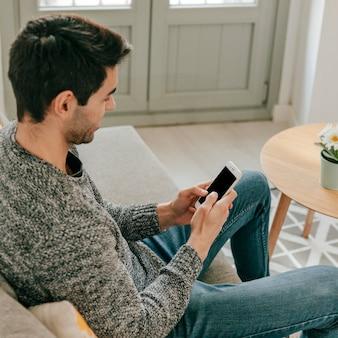 Vrolijke mens die smartphone op bank gebruiken