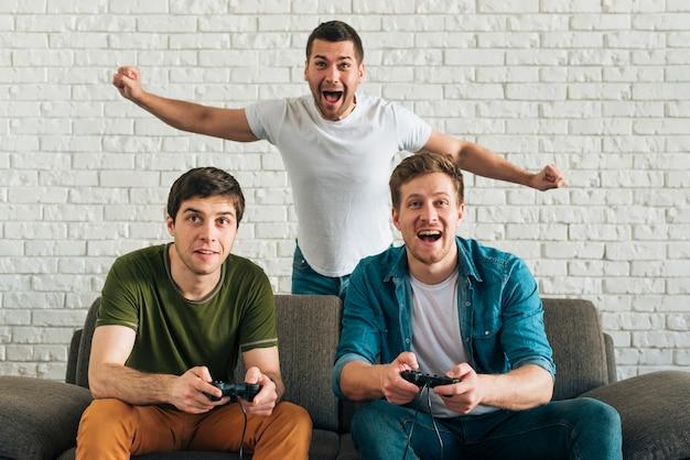Vrolijke mens die voor de vrienden toejuichen die videospelletje thuis spelen