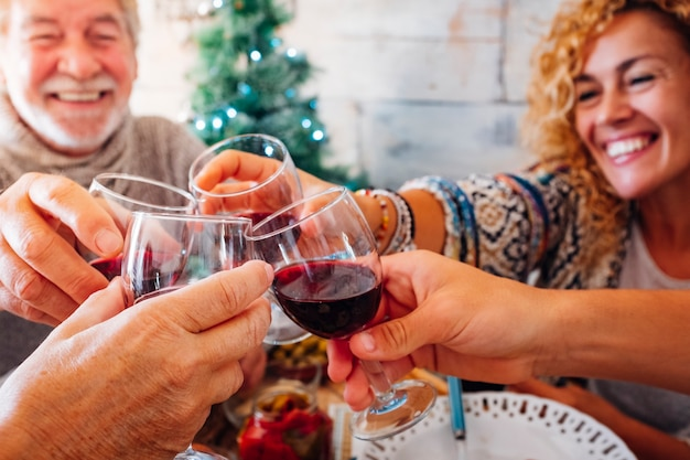 Vrolijke mensen familie en vrienden roosteren met rode wijn