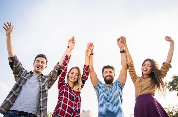 Vrolijke mensen staken hun handen naar de top op straat.