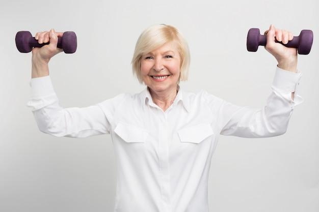 Vrolijke mevrouw traint met lichte gewichten. ze doet dat omdat ze zorgeloos met pensioen gaat en veel tijd heeft om dat te doen.