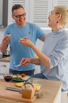 Vrolijke middelbare leeftijd paar glimlachen tijdens het koken lunch samen thuis gezonde gepensioneerde levensstijl