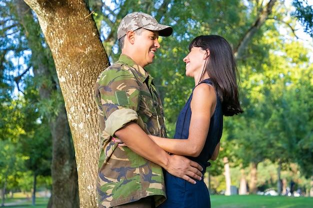 Vrolijke militaire man en zijn gelukkige vrouw praten en knuffelen in stadspark. zijaanzicht, gemiddeld schot. terug naar huis of relatieconcept