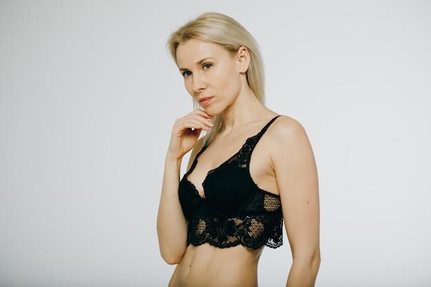 Vrolijke mode vrouw met zwarte slipje, zwarte beha en sexy lingerie